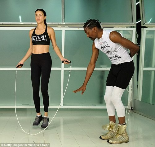 Adriana's trainer, Aerospace co-founder Michael Olajide, is pictured walking the model through a jump rope routine