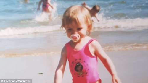 This family photo shows a young Amy as a toddler playing on a beach. Her family have posted a moving tribute video
