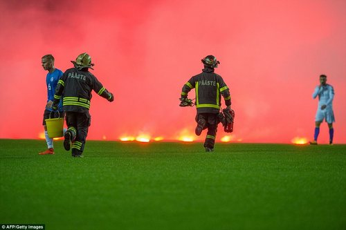 Firemen run on the pitch to take care of the flares thrown by Bosnia fans, armed with sand buckets and fire extinguishers