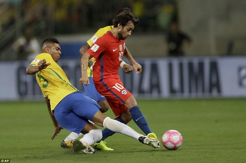 Real Madrid midfielder Casemiro dives in as he tries to win the ball from Chile's Jorge Valdivia