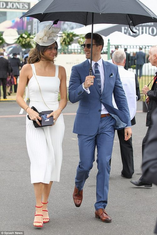 Looking after his lady! Chivalrous Matty shielded Laura from the rain during the day's event