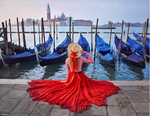 One photo taken in Venice, Italy, shows Nina sitting by a canal wearing a floor-length lipstick-red skirt. She completes the look with a striped top and straw boater