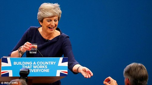Mrs May's conference speech was blighted by a persistent cough (pictured taking a lozenge from Mr Hammond)
