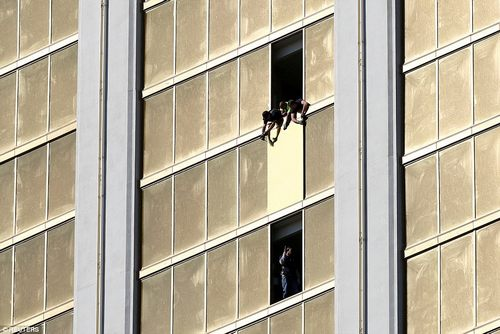 Workers board up a broken window at the Mandalay Bay hotel, where shooter Stephen Paddock conducted his mass shooting along the Las Vegas Strip