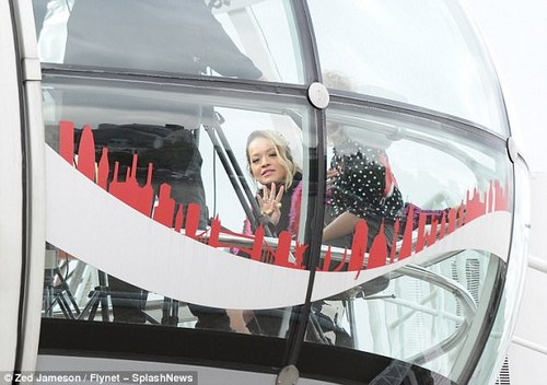Social occasion: The starlet waved down to the onlookers looking up at the tourist attraction
