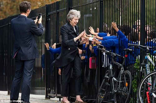 Mrs May is pictured high fiving with primary school pupils at a school in London ahead of her statement to the Commons yesterday