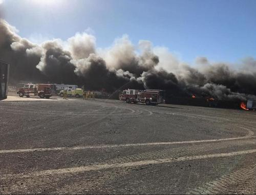 Photo shows flames at an auto salvage yard that destroyed two structures and 50 to 100 cars