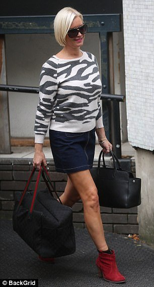 Splash of colour: She tied her look together with red ankle boots, and accessorised with oversized sunglasses as she headed home from the studios