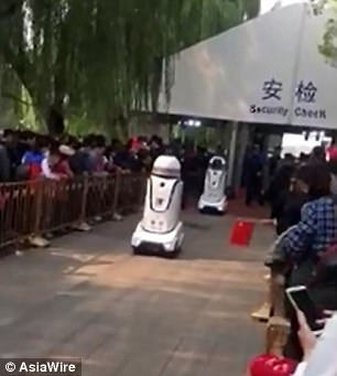 The robot also has a speaker that demands tourists to 'please queue in an orderly fashion and cooperate with security inspections