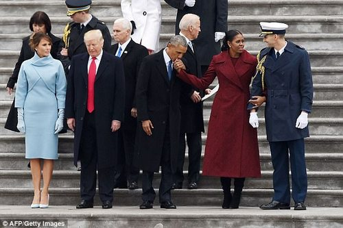 Barack Obama and Michelle Obama share an affectionate moment while Donald Trump looks to the ground and Melania Trump looks at the display of affection inauguration festivities on January 20. Behind the Trumps are Mike and Karen Pence