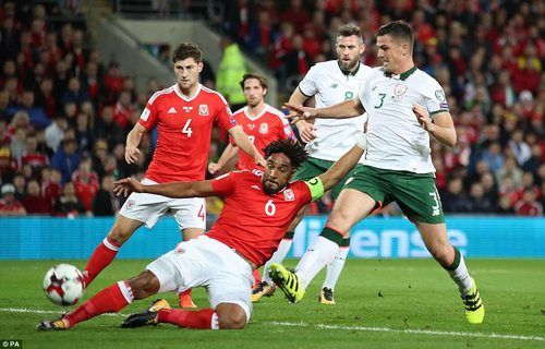 After early Welsh pressure, Ashley Williams is forced to clear his lines after a dangerous ball is drilled into the box
