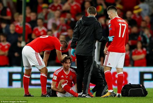 Joe Ledley checks on Allen, who is attended to by the Wales medical stuff, after a landing on his head during an awkward fall