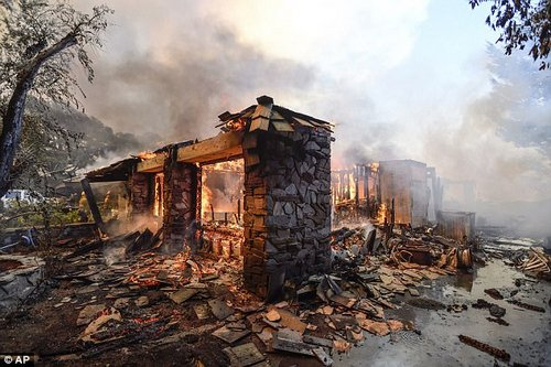 What little is left of a home in Anaheim Hills continues to burn on Monday afternoon