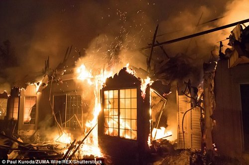 The front of the hotel is consumed by flames after fast-moving fires tore through Santa Rosa, California