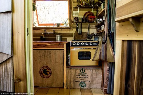 The kitchen area is seen from ground level with the oven on the right and the sink on the left which is in front of a big window