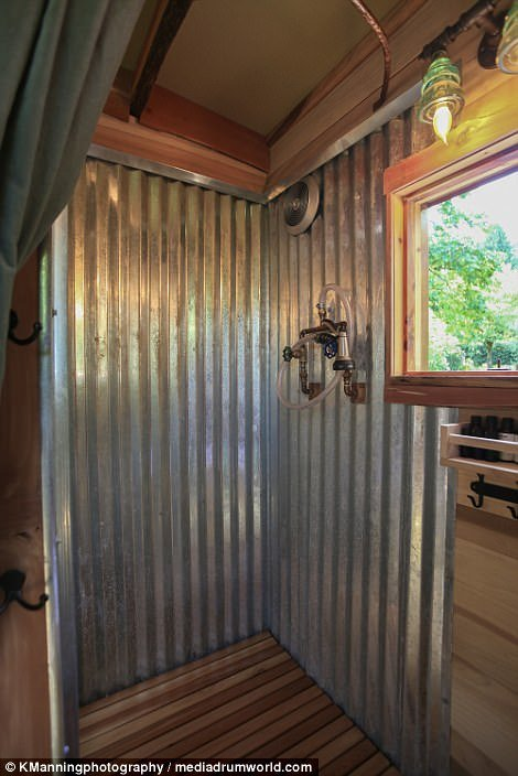 The bathroom, which is located behind the kitchen, consists of a shower head, two taps and corrugated metal sheets above a floor of wooden slats