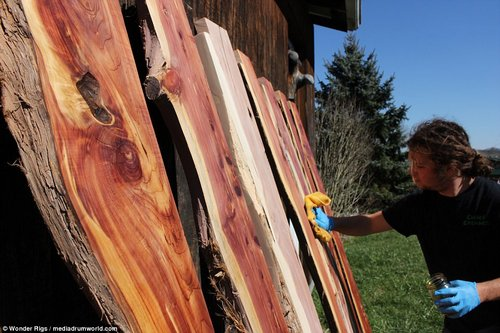 Hard at work: Stevie applies varnish to the interior wood panels of the house before later fitting them in his homely kitchen
