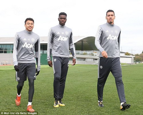 Jesse Lingard, Axel Tuanzebe and Chris Smalling (left-right) wander out to the training pitch