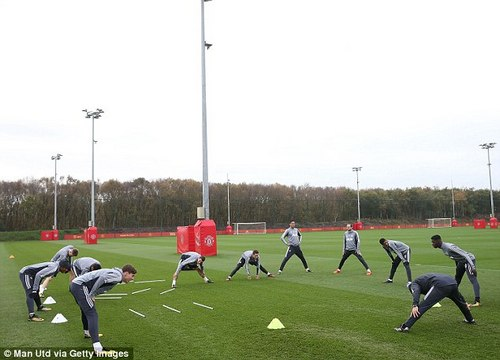 A fitness coach takes the first-team players through their stretches on the plush pitch