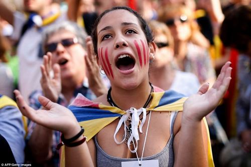 A young woman reacts outside the Catalan parliament in Barcelona after the news filters out to the crowd watching the parliamentary session in the street