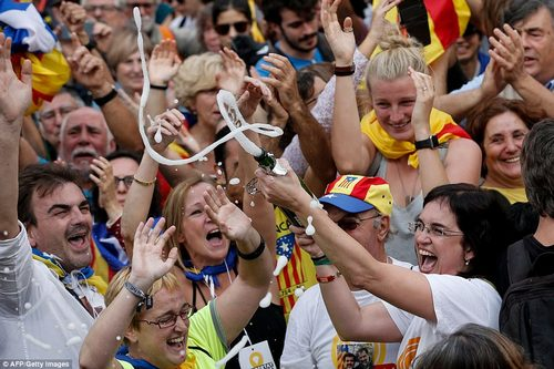 After the vote, Puigdemont said: 'Today our legitimate parliament, that came out of a democratic election, has taken a very important step.' Pictured: Champagne is broken open in celebration of the declaration