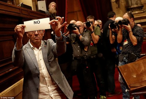 """A member of the Catalan parliament who is opposed to independence holds a """"No"""" ballot during the independence voting session"""