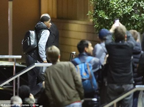 United fans straddle the barrier to get a picture of Marcus Rashford as he arrives at the hotel