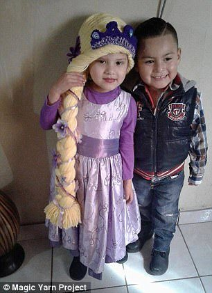 Happy together: This little girl can't help but hold her braid proudly as she poses with a friend