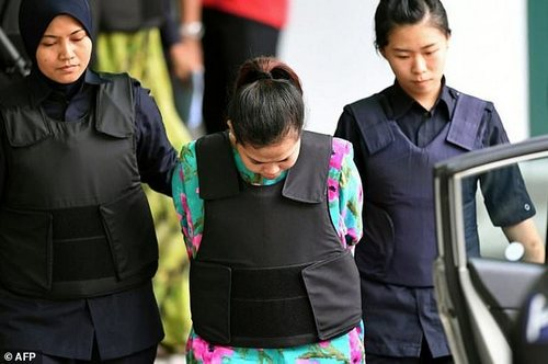Indonesian defendant Siti Aisyah is escorted by police following her appearance at the laboratory in Petaling Jaya outside Kuala Lumpur