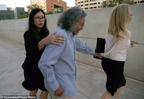 Billionaire founder of Insys Therapeutics John Kapoor, center, is escorted out of U.S. District Court after being arrested earlier Thursday, Oct. 26, 2017, in Phoenix. Kapoor and other defendants in the fraud and racketeering case are accused of offering bribes to doctors to write large numbers of prescriptions for a fentanyl-based pain medication meant only for cancer patients with severe pain. A judge set bail at $1 million for Kapoor, saying he must wear electronic monitoring and surrender his passports. (AP Photo/Ross D. Franklin)