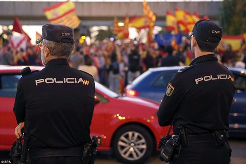 People wave Spanish and Catalan flags as they take part at a demonstration to support Spanish National Police and Civil Guard agents who are located at Barcelona's port in Barcelona. The city is braced for more protests today
