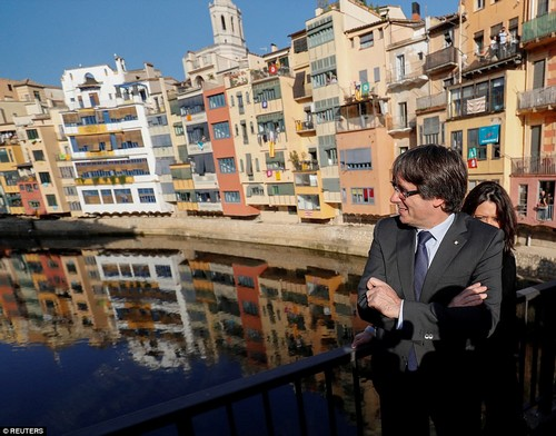 Mr Puigdemont poses on a bridge in front of buildings displaying Catalan flags and pro-independence banners during his walkabout in Girona
