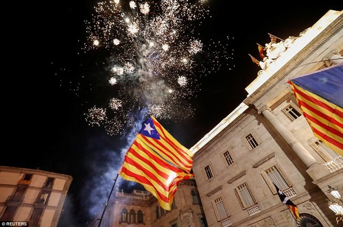 Catalan separatist flags are held up as fireworks go off in Sant Jaume Square in front of the Catalan regional government headquarters during celebrations on Friday night