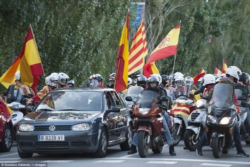 Hundreds of bystanders reacted with smiles and cheers, with many punching the air and waving Spanish flags in response as the motorcade went past