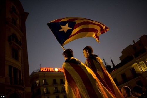 Pro-independence supporters carry an 'Estelada' or independence flag in downtown Barcelona yesterday evening where thousands of people gathered