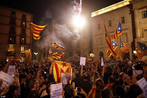 """Pro-independence supporters release fireworks and wave """"estelada"""" flags in the square outside the Palau Generalitat in Barcelona"""