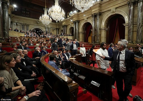 Before Friday's vote, opposition parties stormed out of parliament in protest - with pro-independence MPs draped their empty seats with Catalan flags