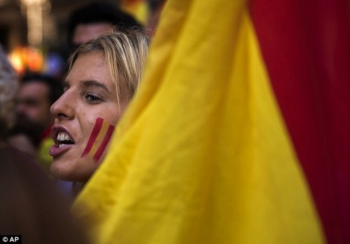 A demonstrator shouts slogans as they march to protest the Catalan government's push for secession from the rest of Spain in downtown Barcelona, Spain