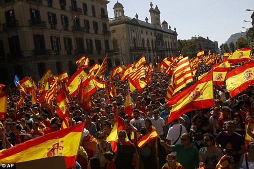 People wave Spanish and Catalan flags during a march in downtown Barcelona, Spain, to protest the Catalan government's push for secession from the rest of Spain