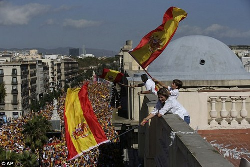 People on a rooftop wave Spanish flags during a march in downtown Barcelona.Hundreds of thousands of flag-waving demonstrators, calling themselves a 'silent majority', packed central Barcelona on Sunday to protest against the plan, which has sparked the country's worst political crisis in a generation