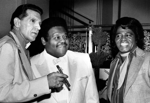 Jerry Lee Lewis, Fats Domino, and James Brown stand together at the Waldorf-Astoria Hotel. They were three of the first inductees into the Rock and Roll Hall of Fame.