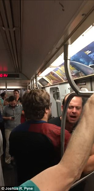 The clip shows the situation escalating as the train moves through the tunnel, with one woman calling him a racist, to which he responds that he's a 'legal scholar' (pictured)