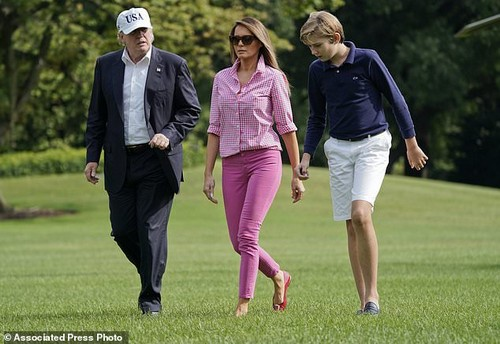 Trump walks with her husband, President Donald Trump, and their 11-year-old son, Barron, on the South Lawn of the White House after returning from a weekend at Camp David this past August