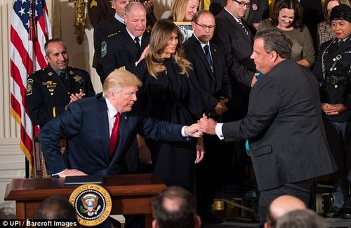 Teamwork: Trump called Christie, the head of his opiod abuse commission, to the stage after signing a director on opioid abuse