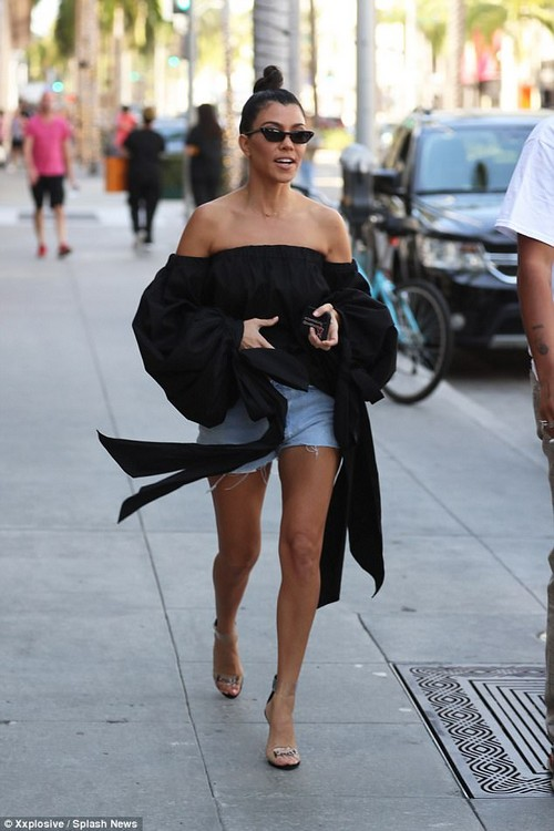 Kourtney showed off her toned and tanned legs in a pair of light blue distressed denim shorts as she walked to the Gucci store in Beverly Hills with her 24-year-old boyfriend and friends