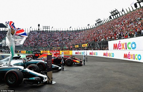 Hamilton waves the Union Flag as he parks his car next to the podium spots where a 'Hammer Time' place is marked for him