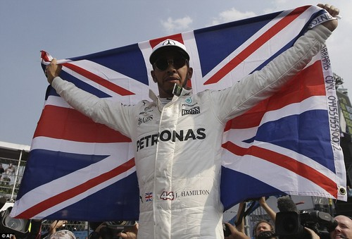 Hamilton poses with the Union Flag having regained the world title despite enduring a terrible race in Mexico