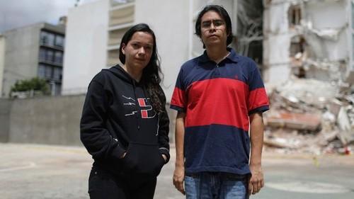 Miriam Anahí Abadia (izq) y su esposo Led Esau Ramírez posan para una foto el 24 de septiembre del 2017 frente al edificio donde vivían en la Ciudad de México, el cual se derrumbó durante el terremoto del 19 de septiembre. Ellos se salvaron porque habían ido a comprar bombillos. (AP Photo/Miguel Tovar)