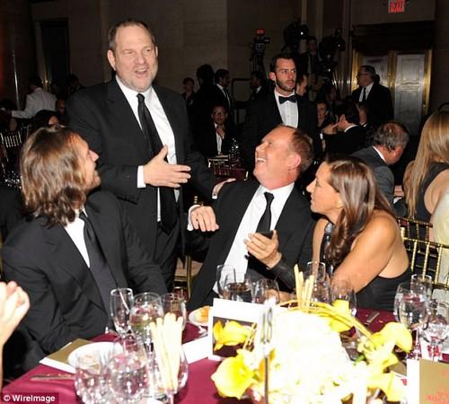 Harvey Weinstein (standing), Michael Kors (center seated) and Donna Karan (around) share a joke at the amfAR New York Gala in 2010
