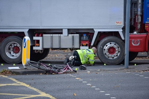 A woman was crushed by a lorry after it crashed with the cyclist at a busy junction in Birmingham